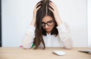 Young tired businesswoman sitting at the table in office